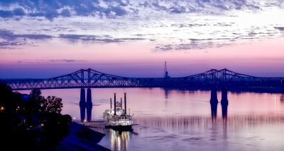 New Orleans Riverfront and Bridge on the Mississippi River at sunset.